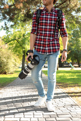 Young male photographer with professional camera in park