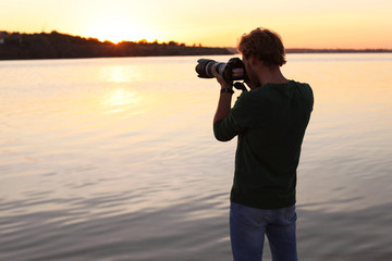 Male photographer taking photo of riverside sunset with professional camera outdoors