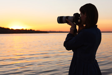 Young female photographer taking photo of riverside sunset with professional camera outdoors