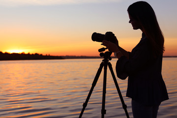 Young female photographer adjusting professional camera on tripod at sunset