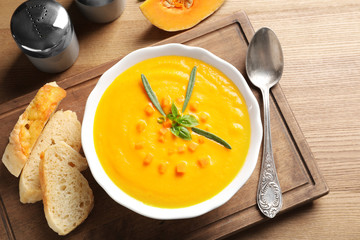 Flat lay composition with bowl of pumpkin soup on wooden background
