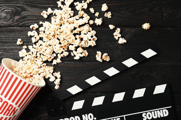 Tasty popcorn and clapperboard on wooden background, top view. Cinema snack