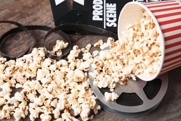 Tasty popcorn, film reel and clapperboard on wooden table. Cinema snack