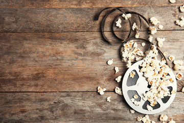 Tasty popcorn and film reel on wooden background, top view with space for text