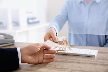 Man receiving money from teller at cash department window, closeup