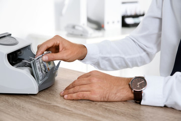 Male teller putting money into currency counting machine at cash department, closeup