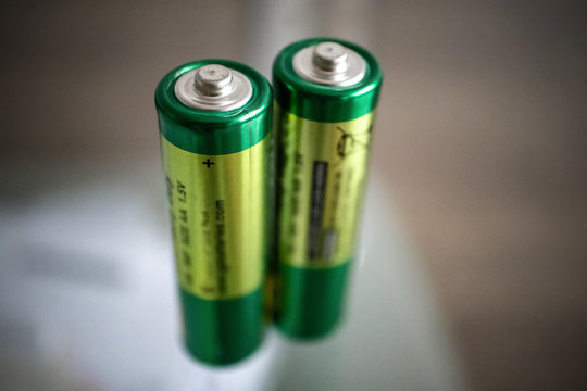 Perspective view of two green AA alkaline batteries