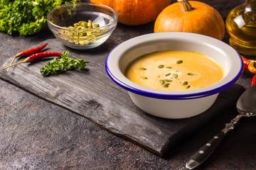 Seasonal autumn food - Spicy pumpkin soup with cream and pumpkin seeds.