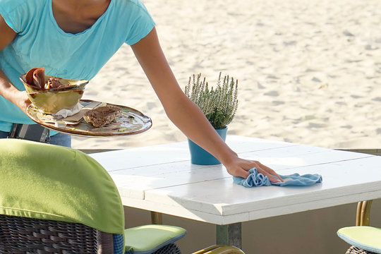 The waitress wipes the table in a cafe on the beach. A waitress is holding a tray with dirty dishes and leftover food. Waitress cleaning the table in a restaurant. The concept of service.