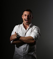 Strong business man laughing with wide opened mouth and sporty biceps arms in white style shirt on dark shadow background. Closeup motivation concept portrait.