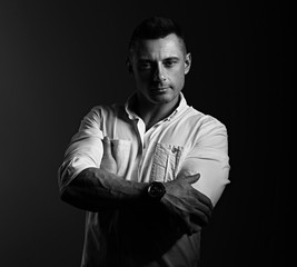 Strong serious business man looking with sporty biceps folded arms in white style shirt on grey dark shadow background. Closeup motivation portrait. Black and white