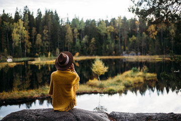 Woman in a yellow poncho and hat in the autumn time in national park Nuuksio, Finland