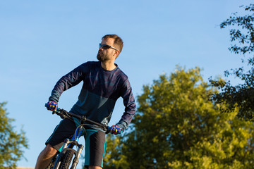 A cyclist rides the hills, Beautiful portrait of a guy on a blue bicycle