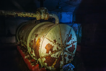 Rusty steel iron barrel in an abandoned Soviet bunker or bomb shelter