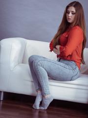 Angry woman sitting on sofa