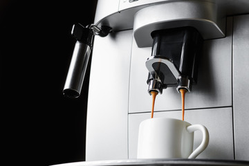 Modern coffee machine brews espresso coffee in white cup