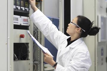Junge Technikerin mit Kittel arbeitet in einem technischen Labor