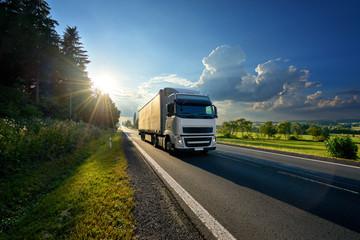 Fotobehang - White truck arriving on the asphalt road in rural landscape in the rays of the sunset