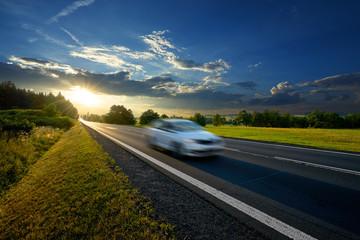 Fotobehang - Motion blurred white passenger car driving on asphalt road in rural landscape at sunset