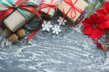 Festive Christmas composition with gifts, boxes, cones, walnuts, red poinsettia flowers on a wooden background with white sprinkles. Copy space. Toned image.n