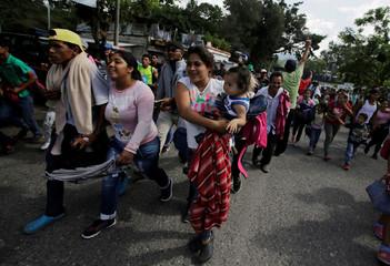 Honduran migrants, part of a caravan trying to reach the U.S., react after crossing the border between Honduras and Guatemala