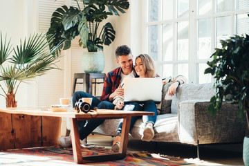 Couple in love. Young family watching TV series using laptop in cozy loft apartment