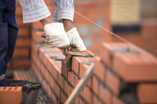 A builder lays bricks wall on a rope with trowel