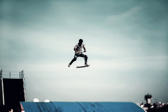 Extreme sport, contrast silhouette of young man, young man doing jump with scooter on background of sky, street culture of young, active lifestyle
