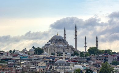 Touristic landmarks from sea voyage on Bosphorus. Cityscape of Istanbul at sunset - old mosque and turkish steamboats, view on Golden Horn.