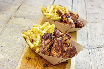 Portion of grilled chicken wings and chips in trays