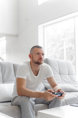 Young man playing tv console on sofa