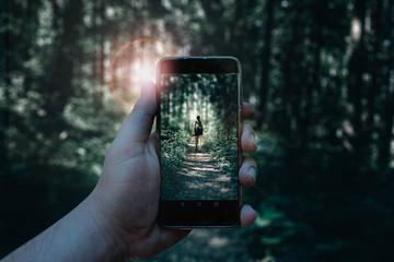Jemand fotografiert Frau im Wald mit dem Handy