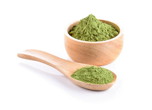 Wooden spoon with powdered matcha green tea in bowl