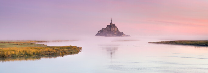 wide angle panorama of pink foggy morning around old castle on the island in France