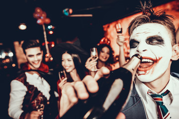 Wall Mural - Young Man in Halloween Costume Drinking Champagne