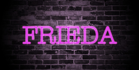 first name Frieda in pink neon on brick wall