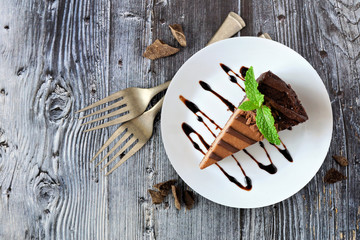Slice of chocolate cheesecake on plate, above view over a rustic gray wood background