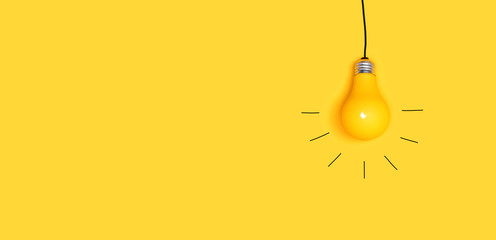 One hanging light bulb on a yellow background Wall mural