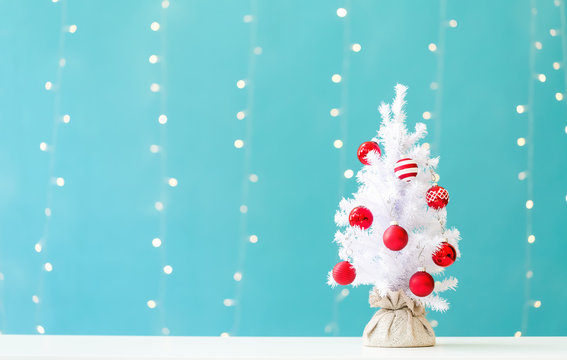Small white christmas tree with baubles on a shiny light blue background