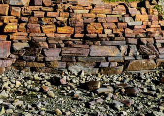 Stacked iron ore stone wall along a beach