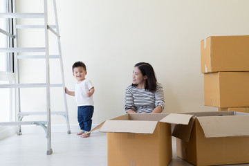 Asian mother and baby boy with cardboard boxes in new house at moving day, Real estate and home family concept