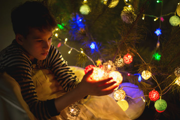 cute young boy in pajamas holds  lights garland in the evening at home. Winter holidays, New year and Christmas celebration concept. soft focus