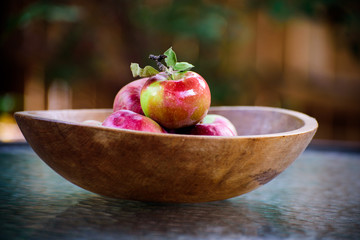 Organic apples in a rustic wooden bowl