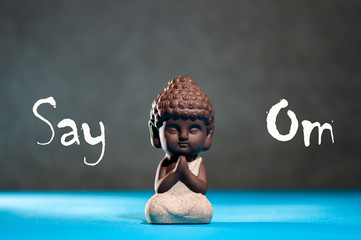 Say Om - phrase with little praying baby buddha. Yoga and meditation concept