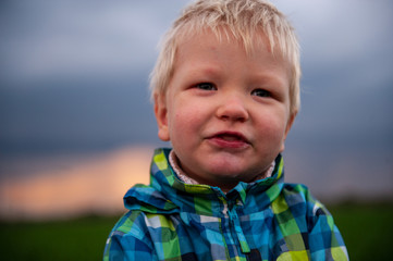 Romantic blondy boy in motley jacket is standing on green field sown with winter wheat against backdrop of rainy clouds. Child spends summer holidays in village. Experience pre-school education.