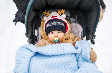 Babywith a pacifier  in a perambulator at a winter day.