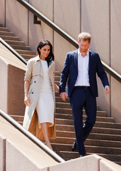 Britain's Prince Harry and wife Meghan, Duchess of Sussex walk during a visit at the Sydney Opera House in Sydney, Australia