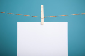Blank Paper Hanging from Clothespin on String, Isolated on Teal