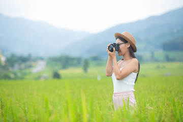 Young woman photograph standing in green grassland.