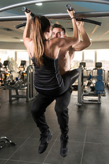 Young Couple Doing Pull Ups In The Gym